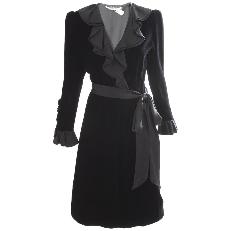 This incredible cocktail dress was made by Yves Saint Laurent, most likely in the 1970s. Made from silk velvet, this dress features black satin ruffle detailing at the collar and neckline, and on the back of each sleeve. Comes with its original