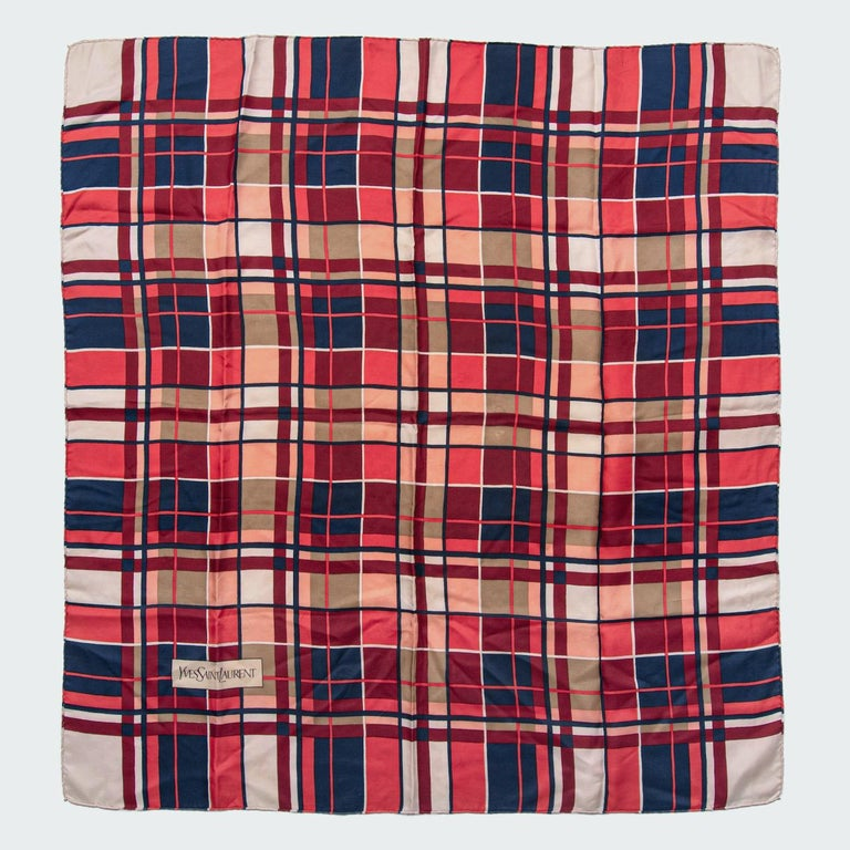 This is a beautiful 1980s Yves Saint Laurent silk scarf. It features one of the plaid prints the brand is renowned for in a wonderful colour combination of coral red, ink blue, maroon and ivory.  The square design is made from a crisp silk twill