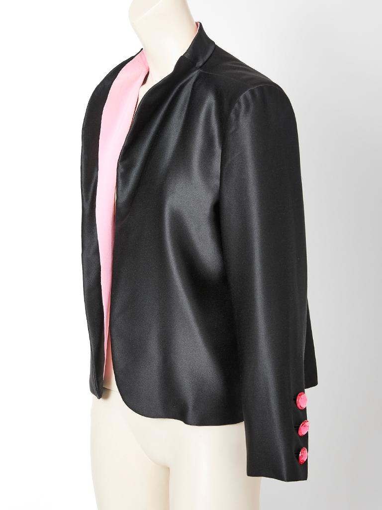 Yves Saint Laurent, couture, black satin evening jacket having a signature YSL pink, silk crepe interior. Rose tone, cut crystal buttons decorate the sleeve cuffs.