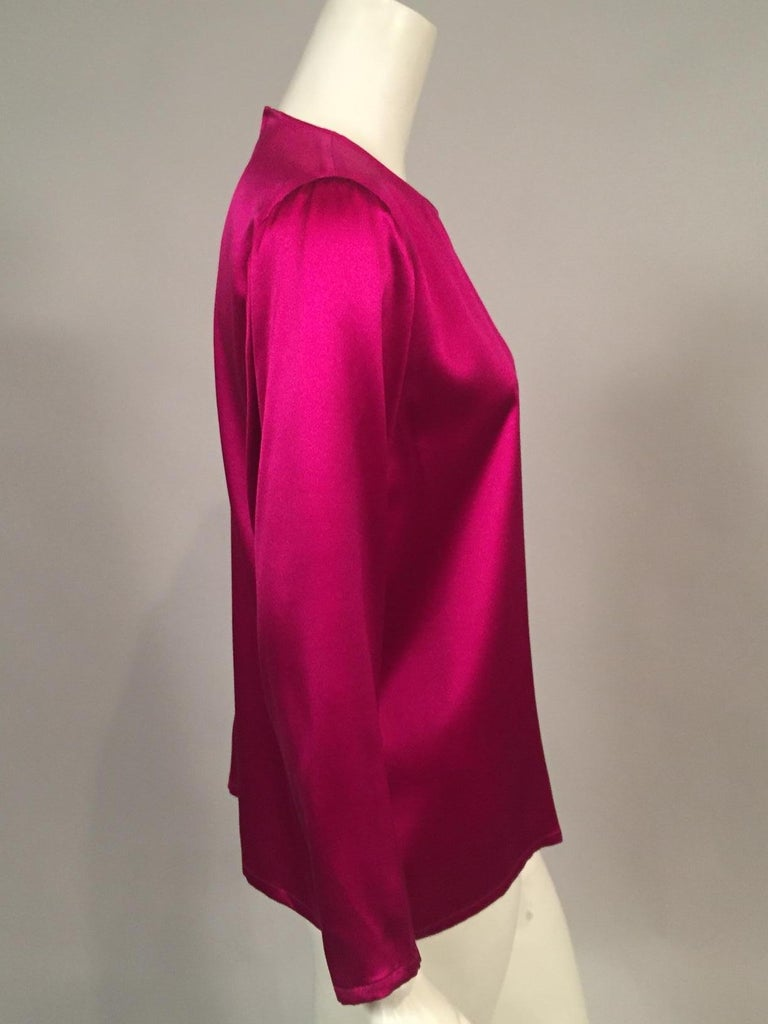 Gorgeous fabric in a gorgeous color makes this YSL blouse a go to piece in your wardrobe. It slips on over your head with a button and loop at the center back. Dress it up or dress it down, it is in excellent condition and marked a vintage size 34.