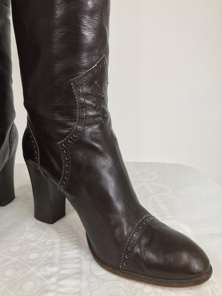 Yves Saint Laurent dark brown leather high heel boots, vintage from the 1970s in very good pre-worn condition. Round toe boots have stacked leather heels. The decorative perforations at the top band, back seam, toe band and ankle fronts are accented