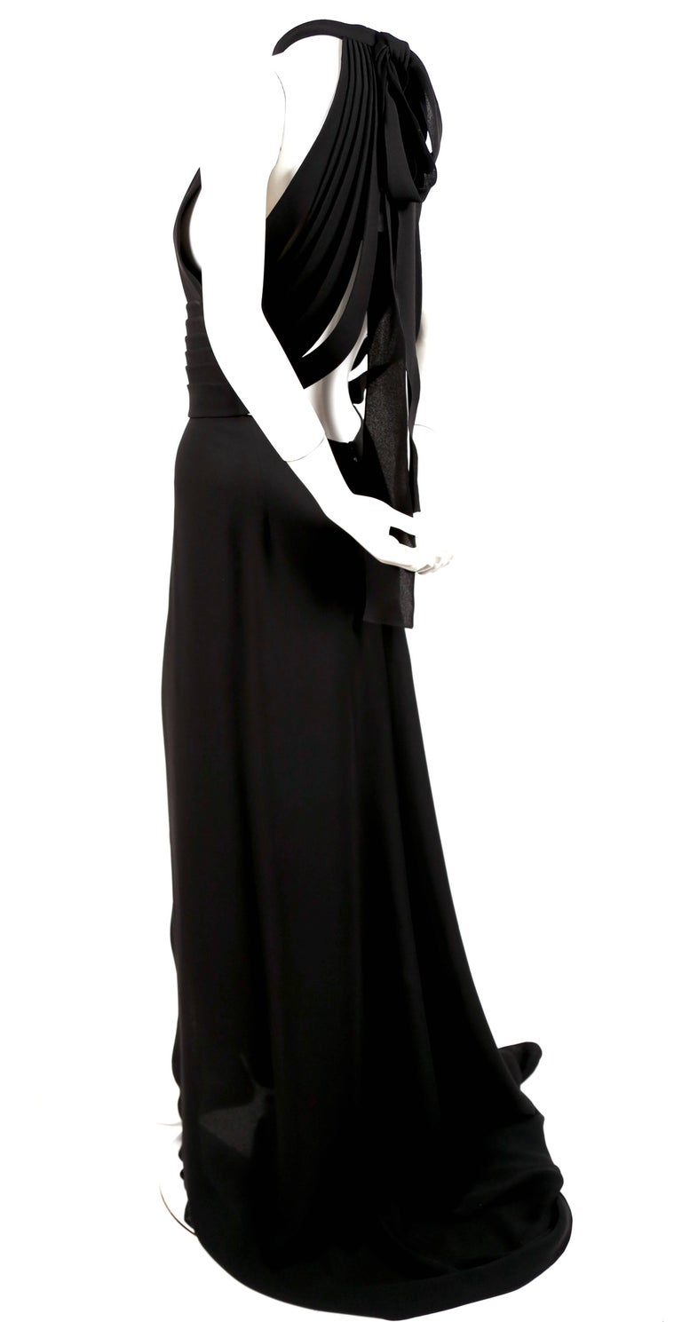 Dramatic jet black silk evening gown with elaborate straps at back from Yves Saint Laurent 'edition soir'. Labeled a French size 42 although this dress runs small and would better fit a French 40. Dress measures approximately 34-36