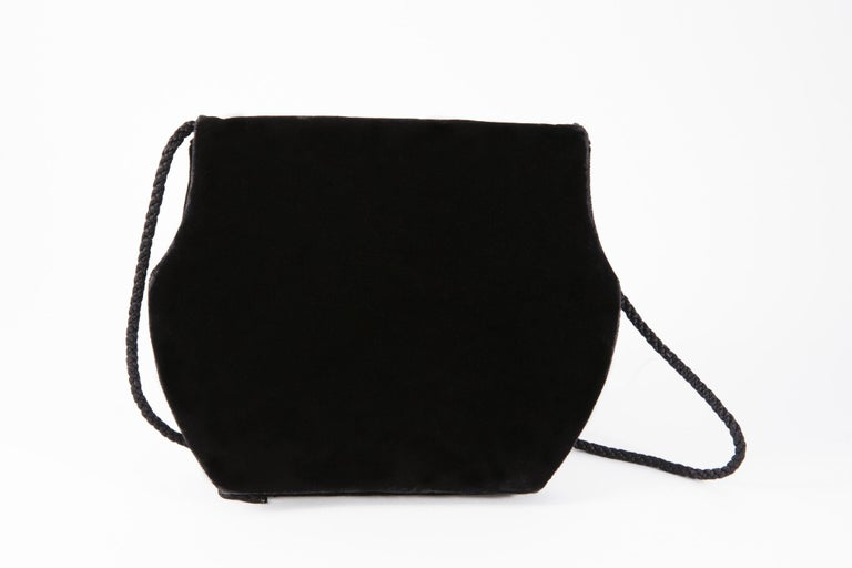 1990s, Yves Saint Laurent black velvet evening shoulder bag featuring a braided shoulder strap (40.9in. (104 cm)), 3 pompons,  a top snap closure, an internal slip pocket, a silk lining.  In good vintage condition. Made in France. 8.2in. (21cm) X