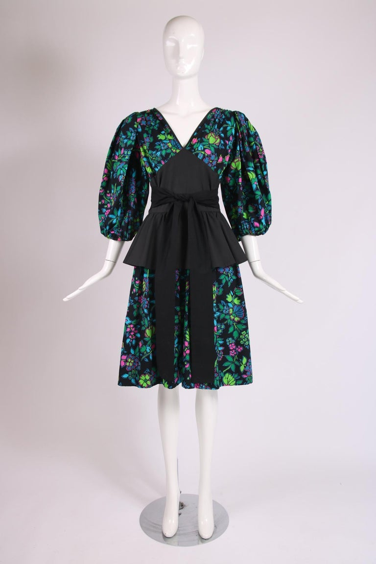 Yves Saint Laurent floral print cotton dress with black yoke at bodice, black peplum, balloon sleeves and black self belt. No size tag - please consult measurements.  Bust - 36