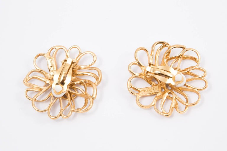Yves Saint Laurent flower gold tone metal earrings featuring a clip on fastening, back plaque logo YSL. 1,9 in. (5cm) X 1,9 in. (5cm)  In excellent vintage condition. Made in France.   We guarantee you will receive this gorgeous item as described
