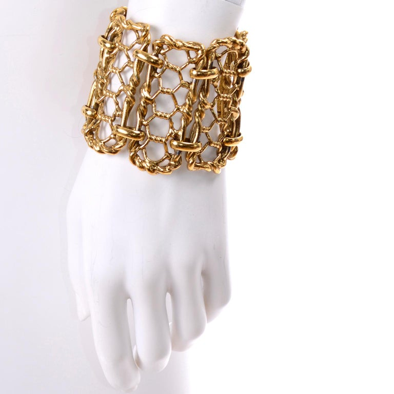 This is an incredible vintage bracelet from Yves Saint Laurent in gold plated metal with a bar clasp. The bracelet has twisted honeycomb links and looks like a cuff on the wrist. We estimate this bracelet to be from the early 1990's. This unique YSL