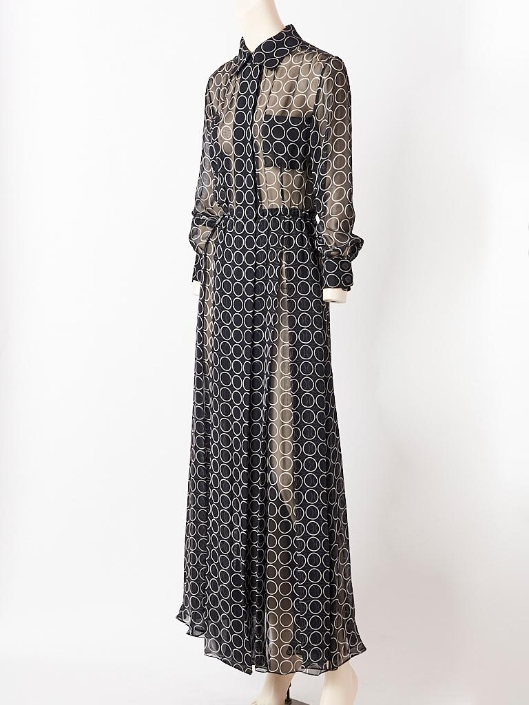 Yves Saint Laurent, black and white,  silk georgette, circle pattern, maxi, shirt dress having hidden front button closures, a small pointed collar, long cuffed sleeves and small, bust pockets. Skirt is very generous with loose box pleating.
