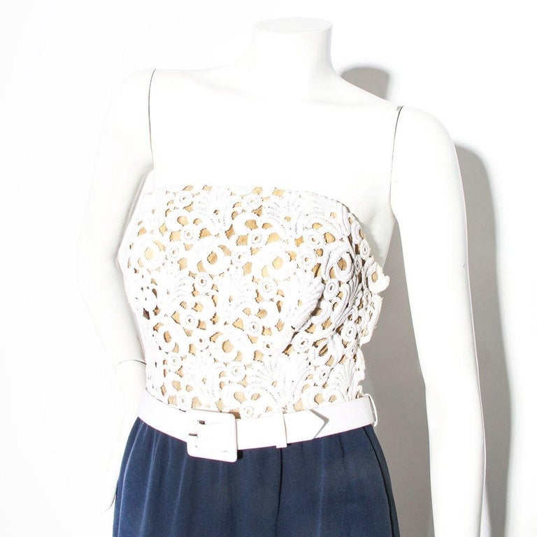 Haute Couture Lace Dress by Yves Saint Laurent  White lace detail on bust White detachable belt  Navy skirt Sleeveless Strapless Structured bust Scoop cut out on back  Column silhouette Left side zip down closure with hook and eye and snap Silk