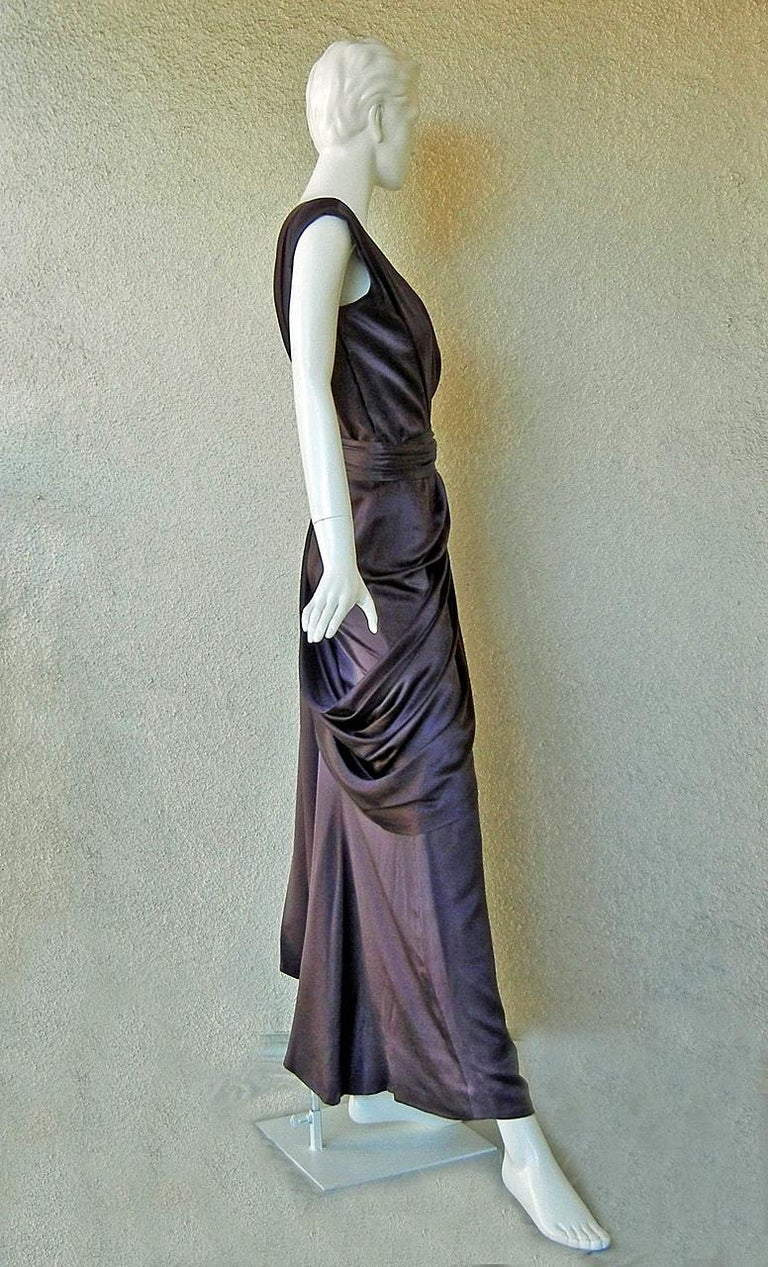 A gown fashioned of deep plum silk charmeuse designed by Yves Saint Laurent from his runway Couture Collection circa 1997-98. With inspiration in style and color from the designer's earlier swag design of the early 1970's. One shoulder with boned