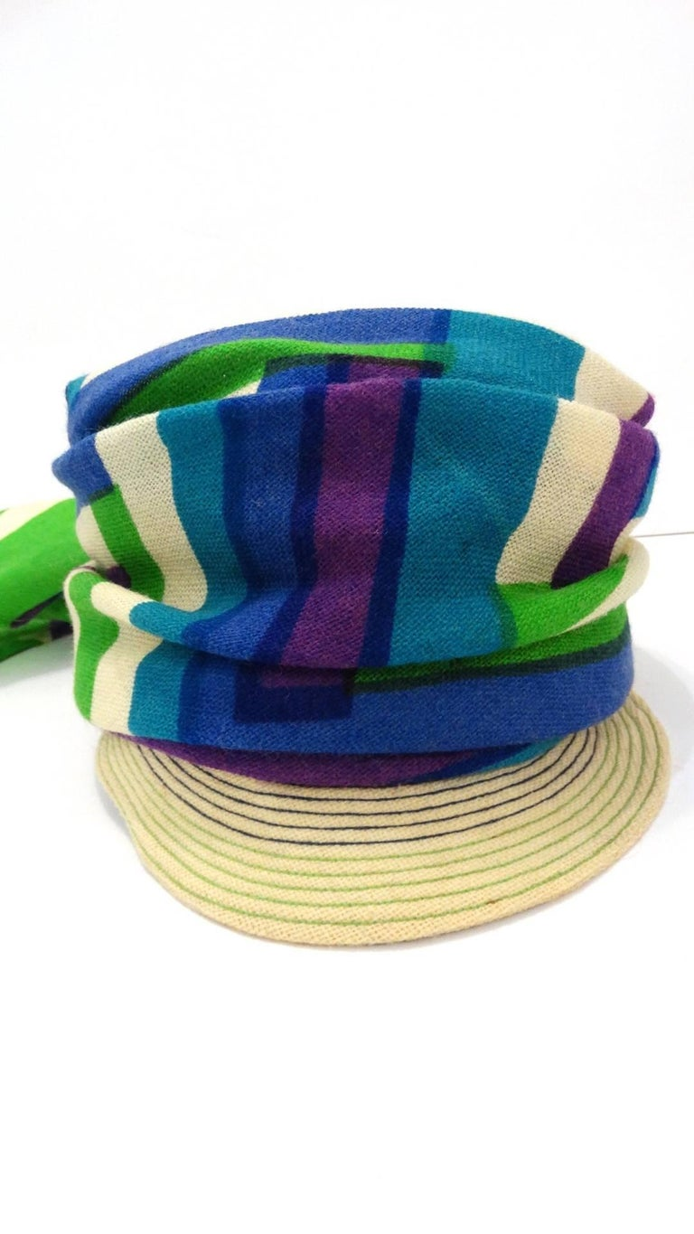 Your perfect summer hat has arrived- with our amazing 1960s Yves Saint Laurent headscarf hat! Woven straw brim with purple and green stitching. Wrapped with blue, violet and green striped scarf, knotted at the back. Lined with grey fabric and
