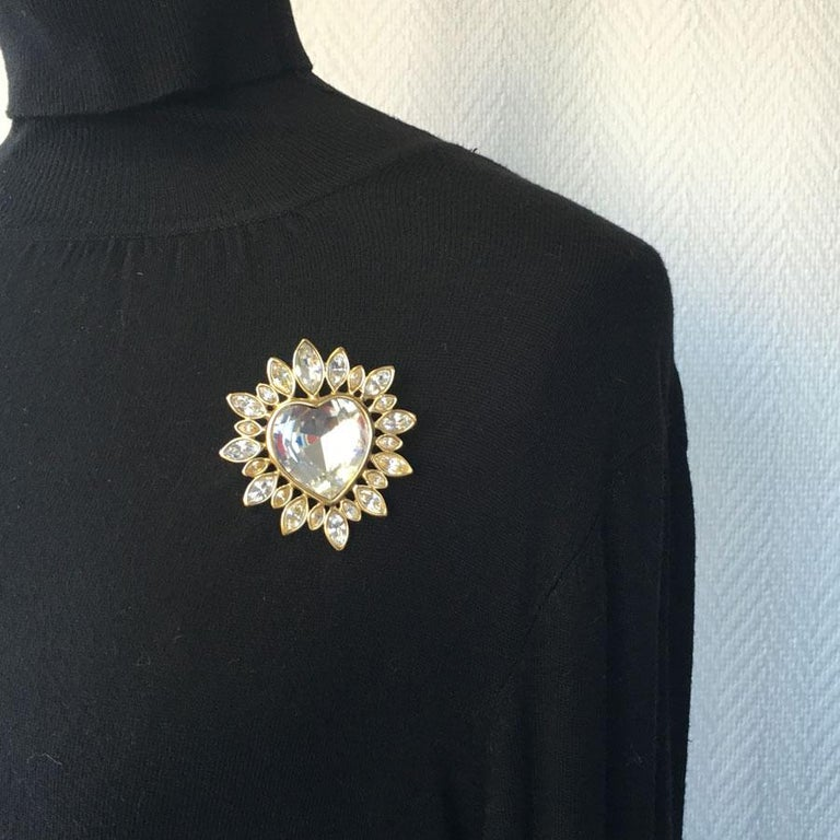Beautiful YSL YVES SAINT LAURENT heart brooch in gold metal and rhinestones. It is available as a pendant, which you can decorate with a ribbon to match your outfit. It is in very good condition, some micro scratches on the heart rhinestones. Brand
