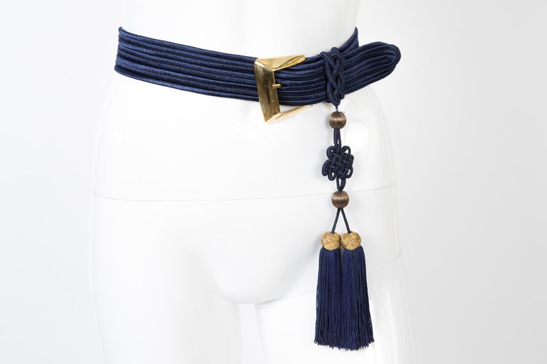 Blue Yves Saint Laurent braided belt featuring a fringed pompons, a gold tone buckle, logo gold tone metallic plaque.  In excellent vintage condition. Made in France.   Maxi Length 35in. (89 cm) Width 1.5in. (4cm) We guarantee you will receive this