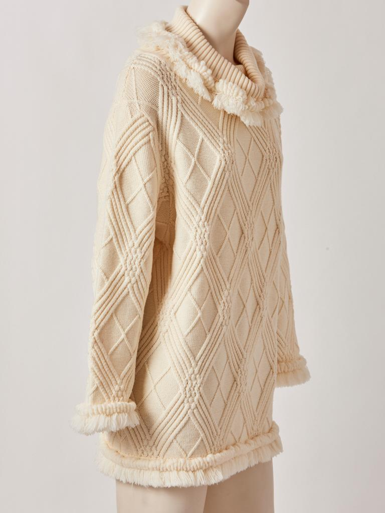 Yves Saint Laurent, Rive Gauche, ivory, wool, textured knit, tunic, having a cowl neck with fringed, detail at the neck, sleeve edges and hem.