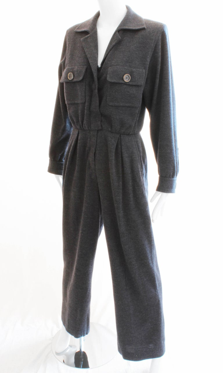 Here's a fabulous charcoal gray wool jumpsuit from Yves Saint Laurent Rive Gauche, likely in the early 1990s. Made from 100% wool, this piece features chest pockets and hip pockets, and long sleeves which can be pushed up to the elbows. Partially