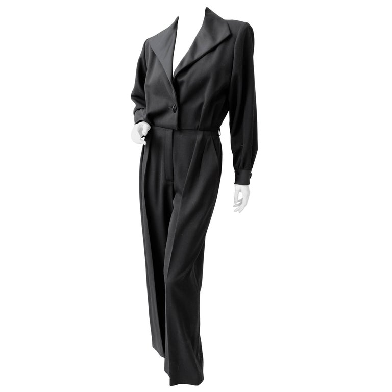 This incredibly chic black jumpsuit was made by Yves Saint Laurent Rive Gauche, most likely in the early 1990s.  Made from wool with silk satin trim, it features YSL's iconic Le Smoking theme in a very sleek jumpsuit with low cut neckline.