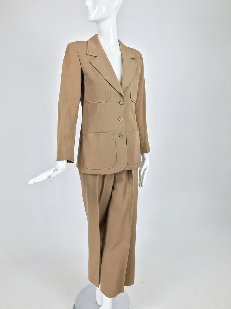 Yves Saint Laurent khaki tan wool twill 4 patch pocket pant suit from the 1970s. An early Rive Gauche pantsuit of flat wool twill, mid-light weight. The single breasted jacket closes at the front with buttons, there are 4 patch pockets, breast and