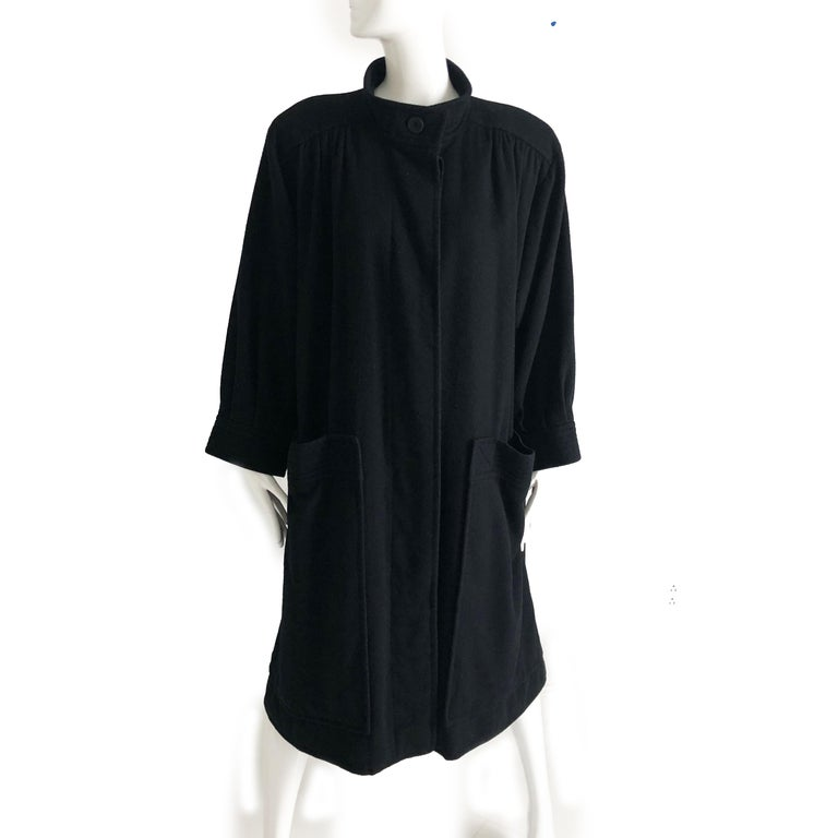 Authentic, preowned, vintage Yves Saint Laurent Rive Gauche long black wool coat, likely from the late 70s. Fully-lined w/shoulder pads and two huge side pockets. Fastens with 5 hidden buttons; 1 exposed button at collar. Preowned/vintage w/some