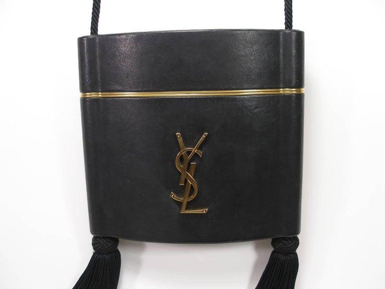 Magnifique Minaudiére YSL in Vintage style      100% Agneau / calf leather      Black color     Pièces en métal bronze     Doublure en cuir    Dimensions 17.5 X 16 X 5cm    Strap : approx 130 cm    Actuelle collection    Rétail price 2150 usd