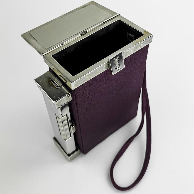 YSL minaudière in purple fabric and silver plated metal. Signed YSL on its opening button. It is rectangular and dressed in purple fabric. Initially perfectly adapted to your cigarettes and equipped with a lighter, you can carry it by hand during