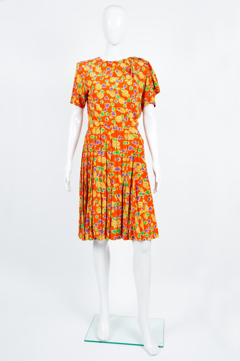 1993s Yves Saint Laurent multico silk dress featuring a jewel pattern, short sleeves,  a fancy button, a pleated skirt part, a wrapped detail on one shoulder. See Catwalk photo same color way.  100% silk In excellent vintage condition. Made in