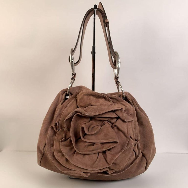 Yves Saint Laurent 'Nadja Rose' Shoulder Bag, crafted in pink nude suede. It features a flap closure with a ruffled rose detail on the front and a drawstring closure. Brown suede lining. 1 side zip pocket and 1 side open pocket inside. 'Yves Saint