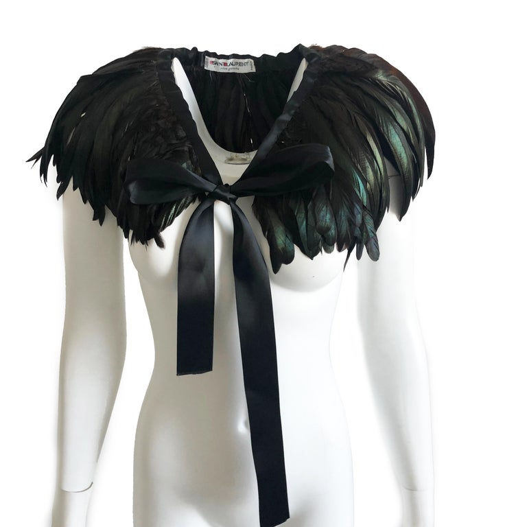 This incredible feathered cape or oversized collar was made by Yves Saint Laurent in the late 1970s. Constructed with iridescent emerald, bronze and black feathers, this piece fastens with long black silk ties. Preowned/vintage with minimal signs of