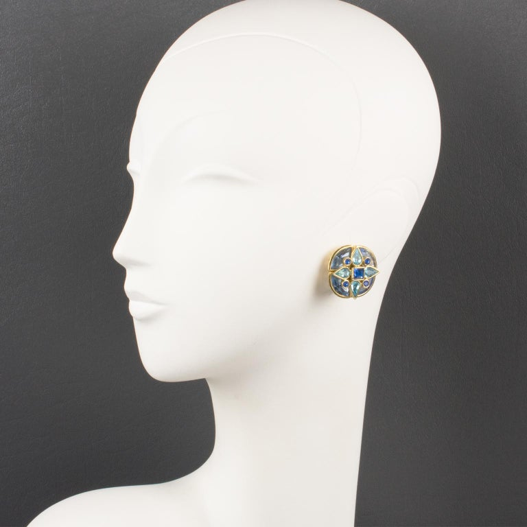 Gorgeous Yves Saint Laurent Paris floral clip-on earrings. Gilt metal flower framing topped with glass rhinestones in assorted shape and colors. Blue range tones in baby blue, bright blue and lavender blue. Engraved marking on fastenings: