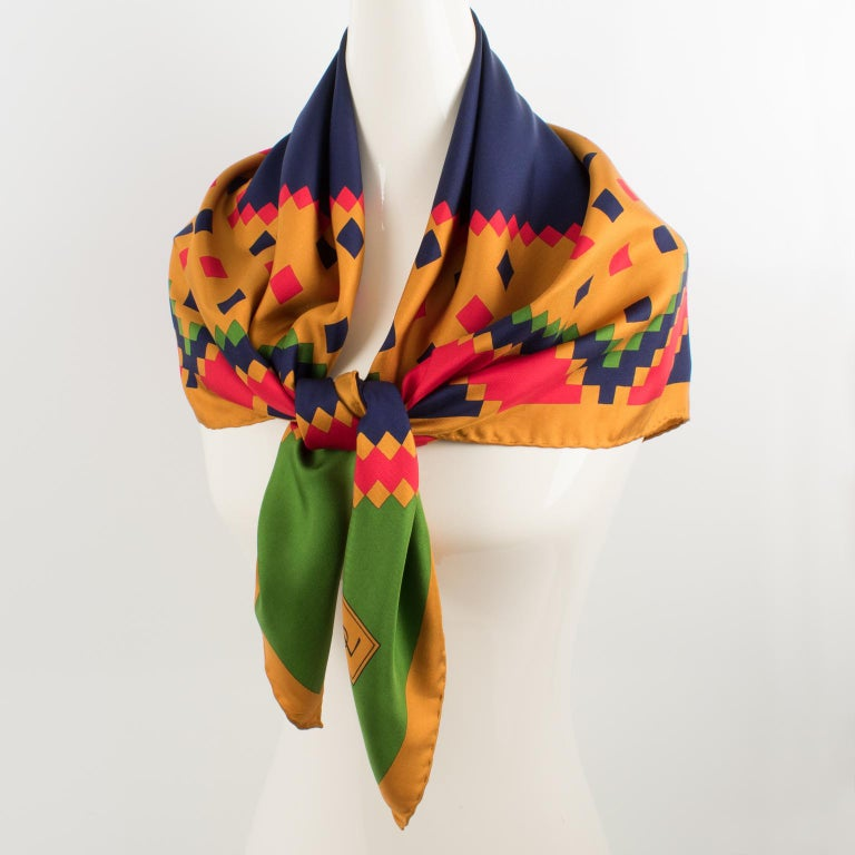 Beautiful silk scarf by Yves Saint Laurent Paris in assorted colors featuring a geometric design print with a YSL signature on the bottom left corner. The colors are bright and vibrant with a combination of navy blue, bright red, and crocodile green