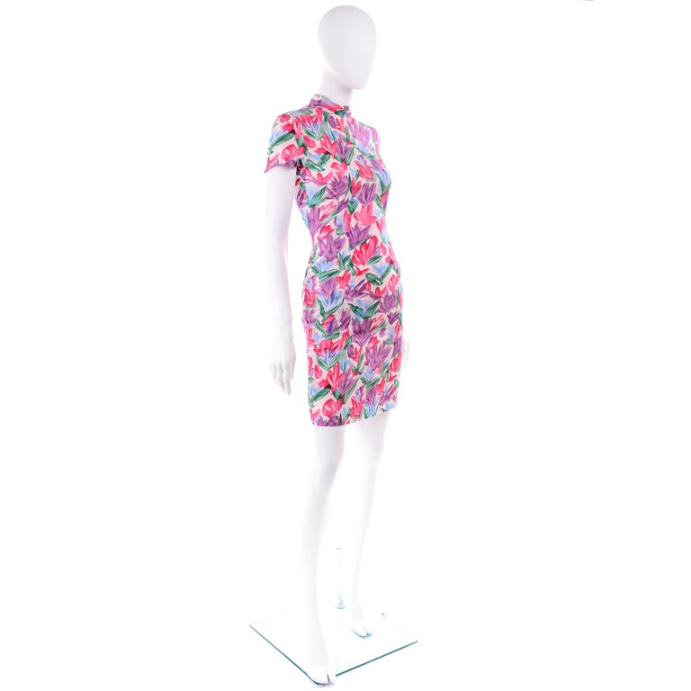 This is a pretty silk dress designed by Yves Saint Laurent, in a magenta pink, purple, blue and green floral print that resembles abstract tulips.  The dress is fully lined and closes with a kdd seamless zipper and a hook and eye.  The sheath style