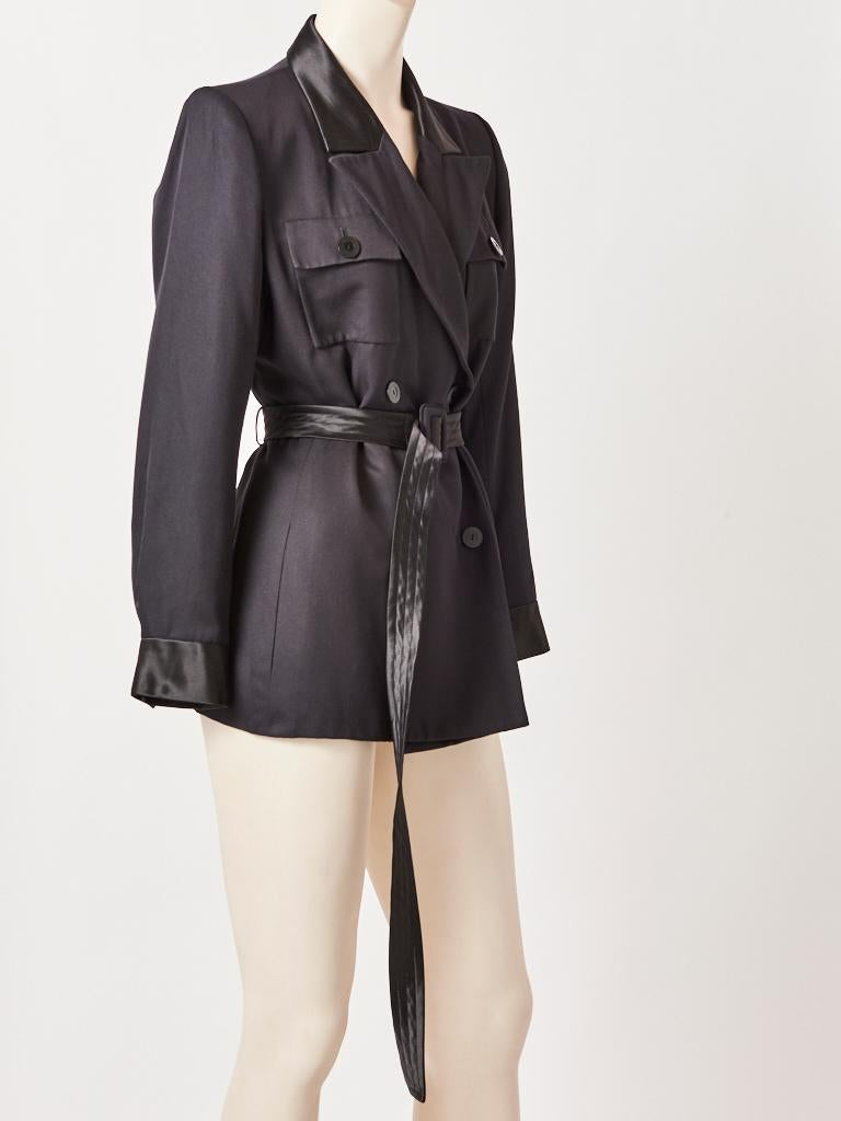 Yves Saint Laurent, Rive Gauche, black, silk, belted, double breasted, Safari/Tuxedo jacket, having wide lapels, breast pockets and a long satin belt. C. 1980's.