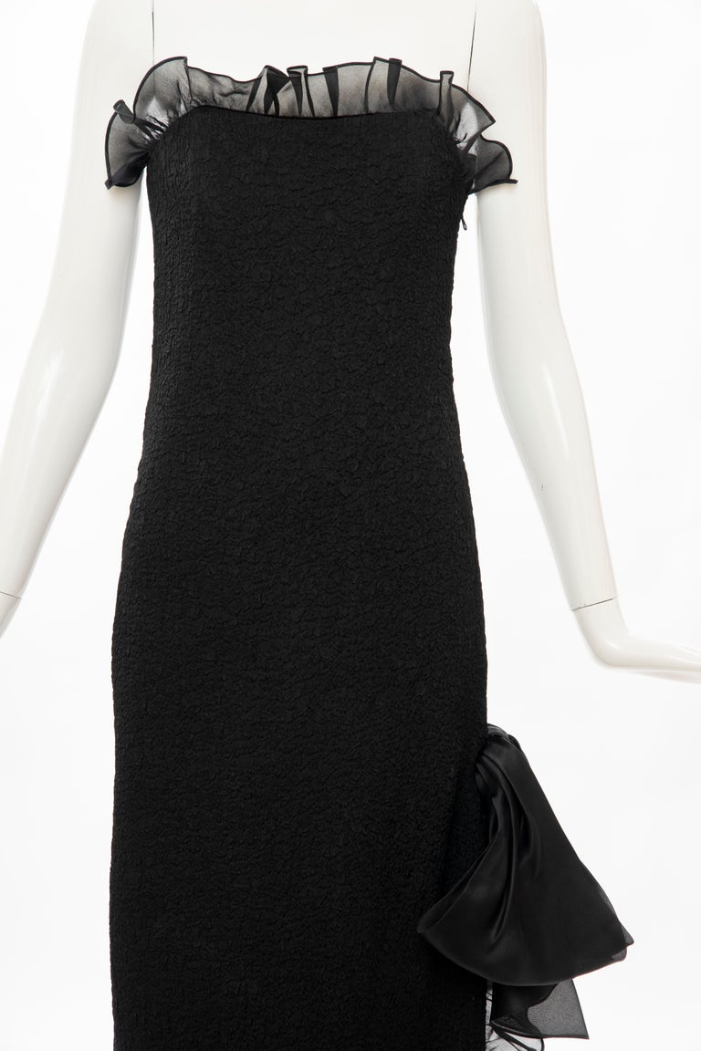 Yves Saint Laurent Rive Gauche, Circa: 1980's black puckered silk column strapless evening dress with straight cut bodice top and high left side slit trimmed with black satin bound organza ruffle, the slit having an oversized bow at the thigh and
