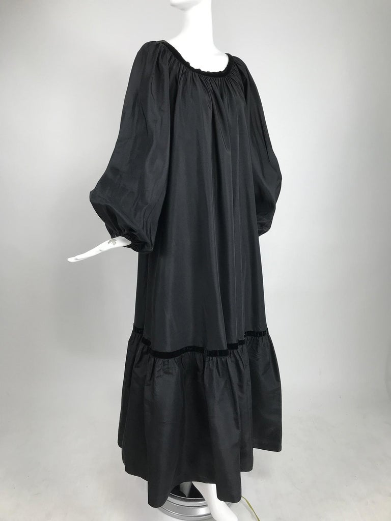 Yves Saint Laurent Rive Gauche black silk taffeta gown from the 1970s. Gypsy/peasant style gown has a open neckline, long very full raglan sleeves have cased elastic cuffs. The dress is gathered at the neck line and falls full to a deep ruffle hem.