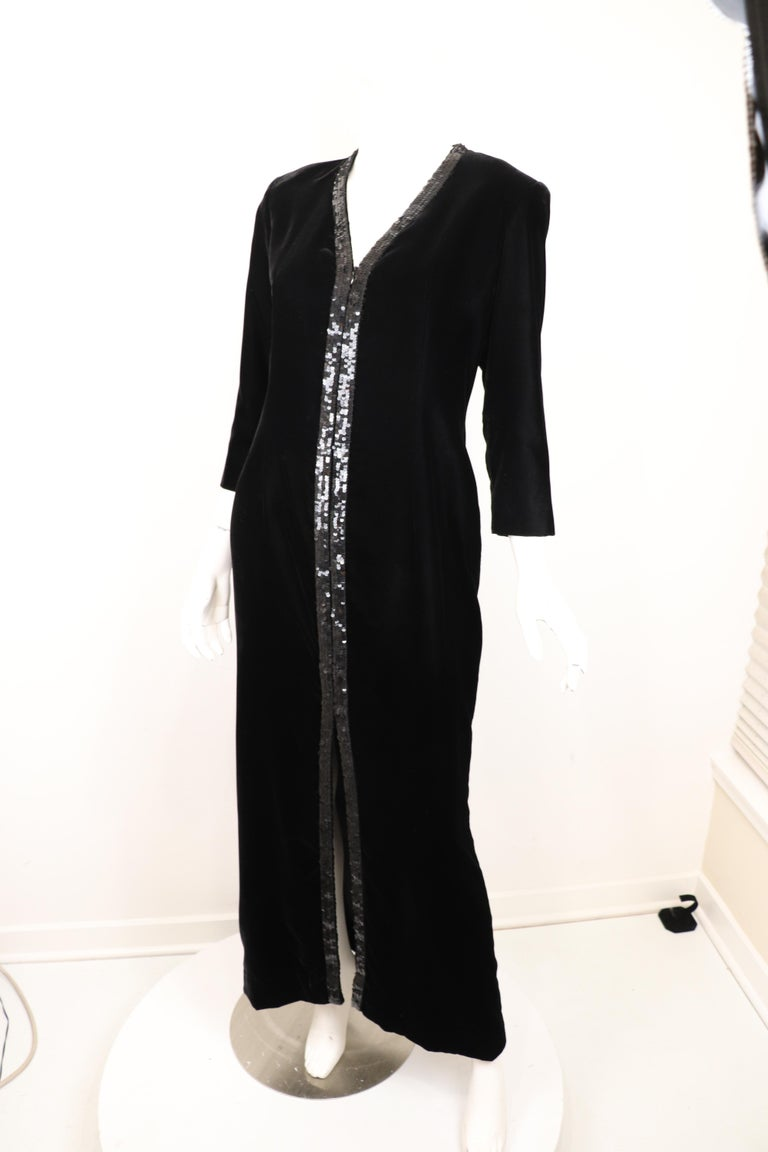 This luxurious Yves Saint Laurent Rive Gauche vintage column gown showcases a soft black velvet with 3/4 length sleeves and a black sequins trim that extends from the neckline, alongside the front zipper, to the front slit. Zipper unzips to about