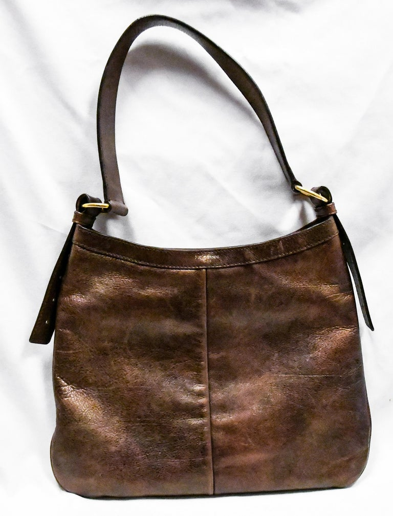 Yves Saint Laurent's Tom Ford, designed the Byzance Maltese Cross jeweled era during his stay at YSL.  This metallic bronze leather hobo bag was one of many of his creative designs produced with the Byzance look.  This adjustable stud decorated
