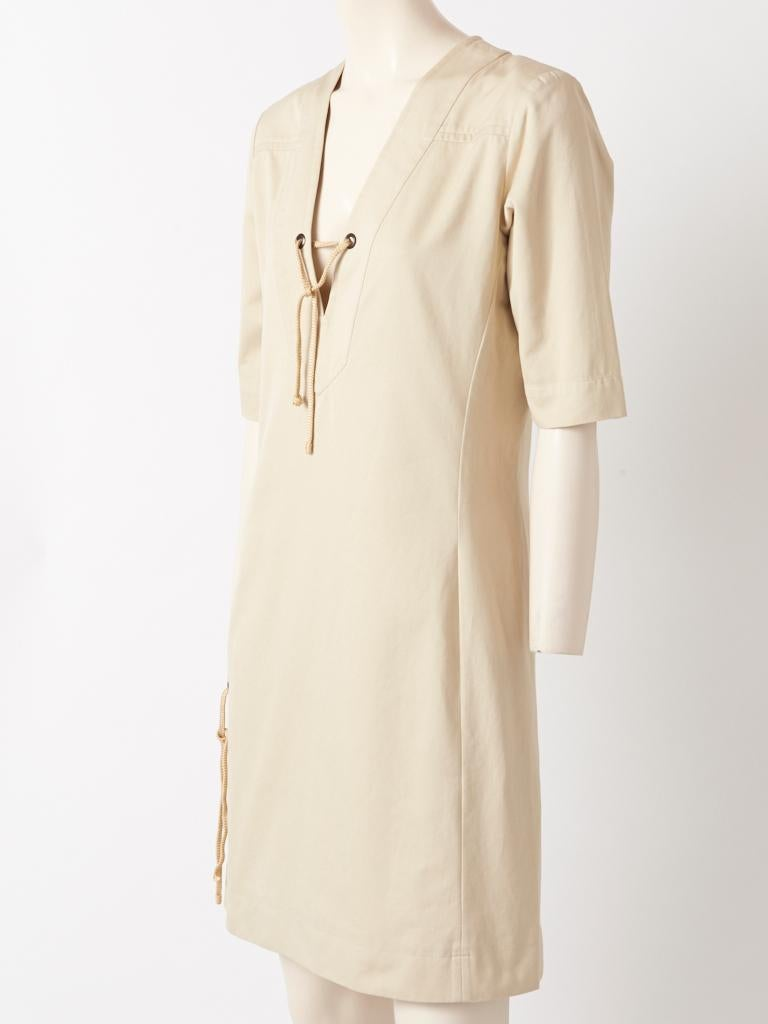 Yves Saint Laurent, Rive Gauche, pale khaki, cotton twill, safari style dress from 1991, having a v neckllne, 3/4 sleeves and deep side slits. Lacing details are at the neckline and sides, Hidden side zippers allow for easy access into the dress.