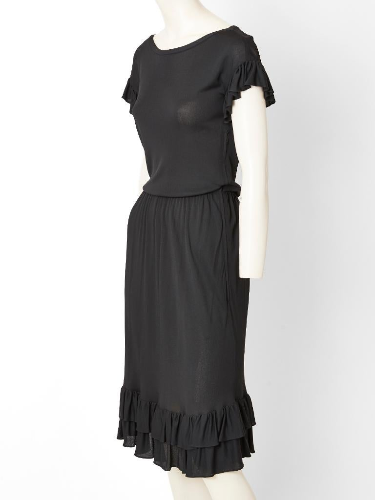 Yves Saint Laurent,  Rive Gauche, black jersey, day dress having ruffled accents at the hem and sleeve edging. Dress is gathered at the waist with a scoop neckline.