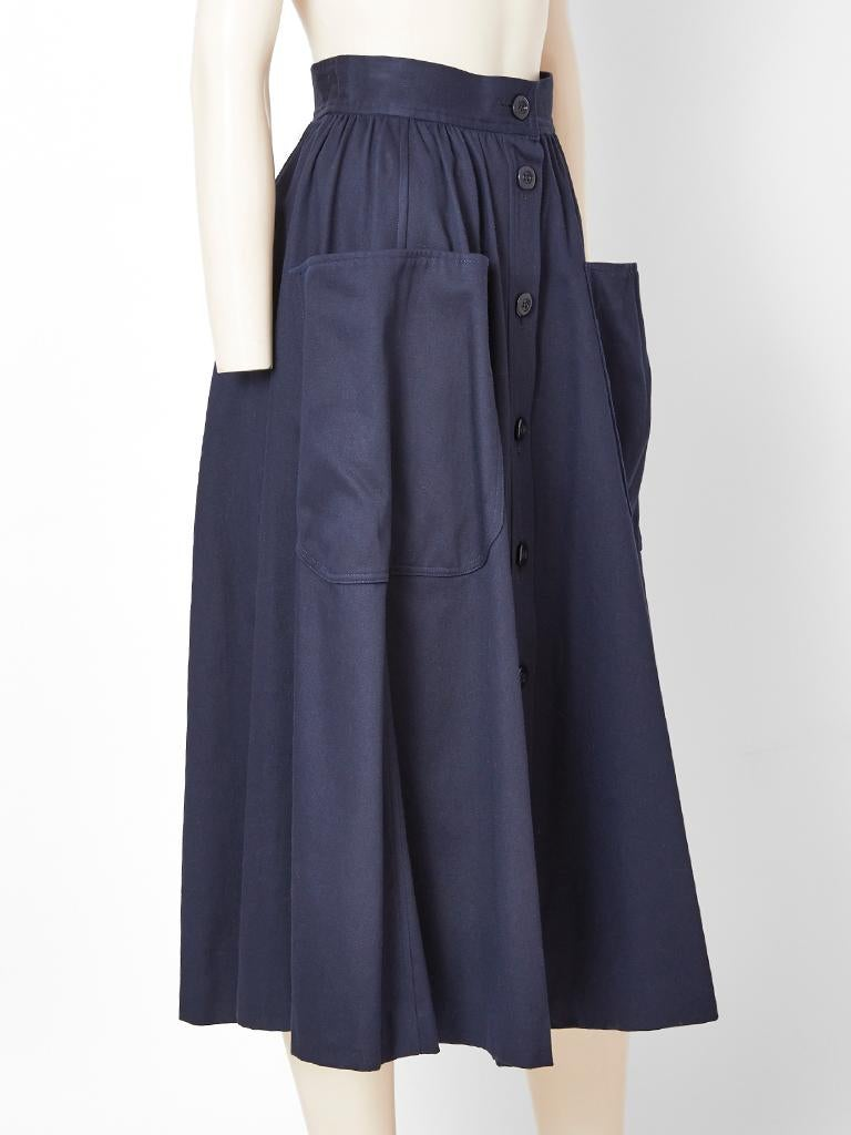 Yves Saint Laurent, Rive Gauche, navy blue cotton, midi skirt, having a gathered waist, center front button closures going down to the hem and large patch side pockets.