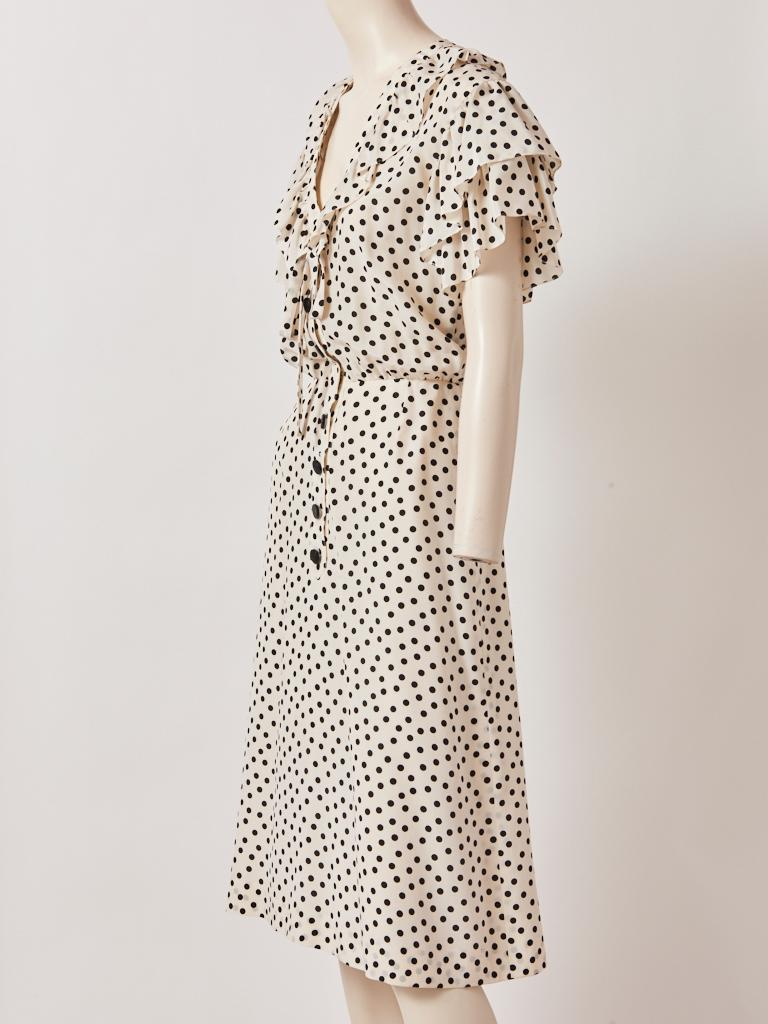 Yves Saint Laurent, Rive Gauche, ivory silk, day dress, having a black polka dot pattern, ruffles along a deep v neckline, and a tie that can be made into a loose bow. The shoulders drop having a double, tiered ruffle sleeve ending at the elbow.