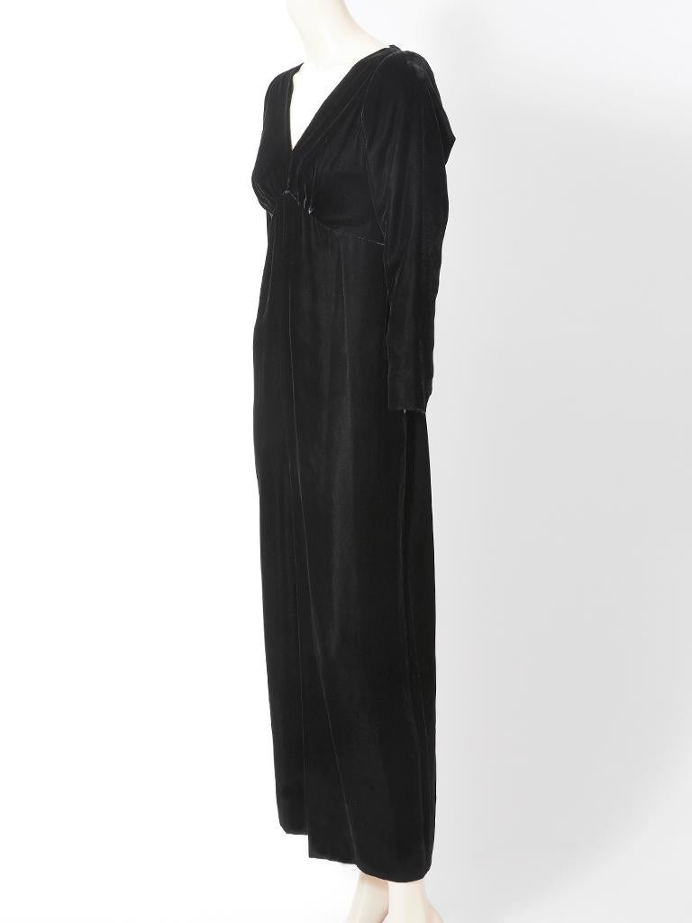 Yves Saint Laurent, black velvet, long sleeve, evening gown, having a deep V neckline, empire waist with some gathering under the bust and a deep slit at the center front.