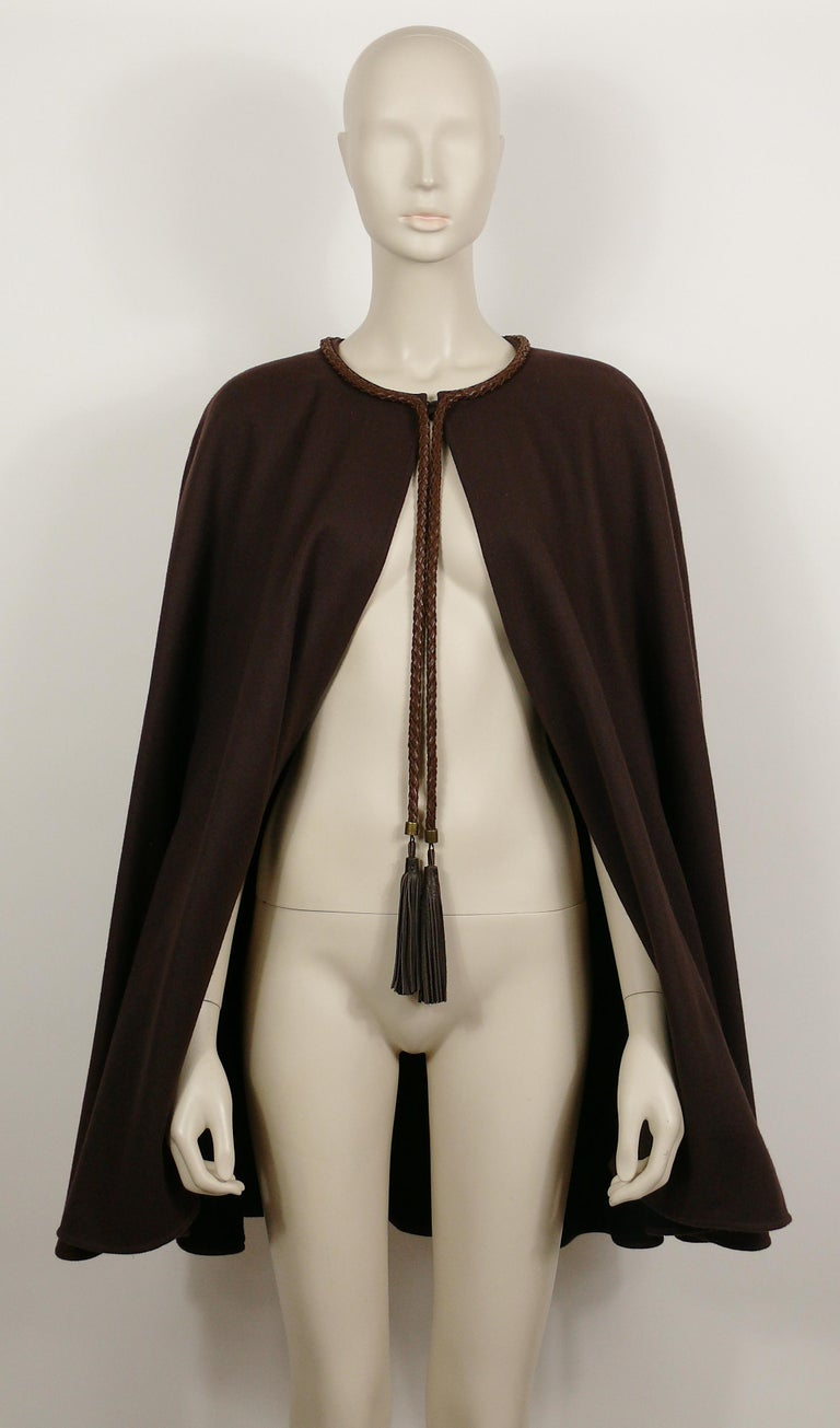 YVES SAINT LAURENT Rive Gauche vintage brown cape featuring leather tassels and breaded trim.  Single breast buttoning. Antiqued bronze toned hardware. Fully lined.  Label reads SAINT LAURENT Rive Gauche Paris. Made in France.  Size tag reads :