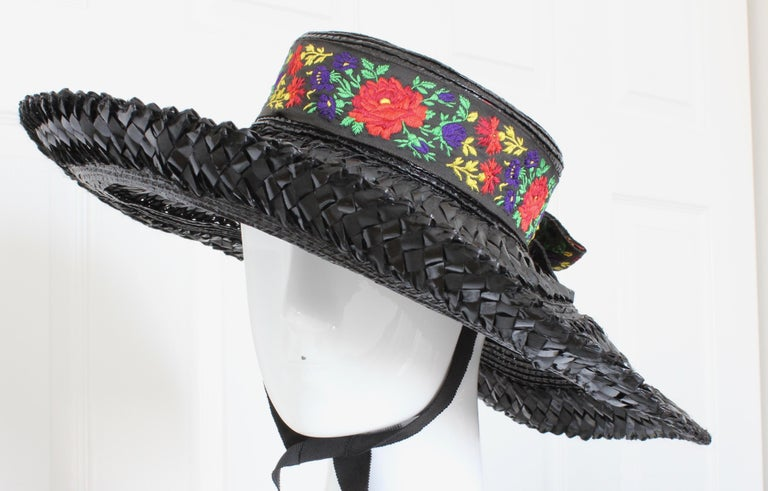 This fabulous black straw hat was made by Yves Saint Laurent Rive Gauche, most likely in the 1970s.  It features a wide floppy brim, brilliant colored florals trimming the crown and as a bow in back, and long grosgrain ties attached to the interior.