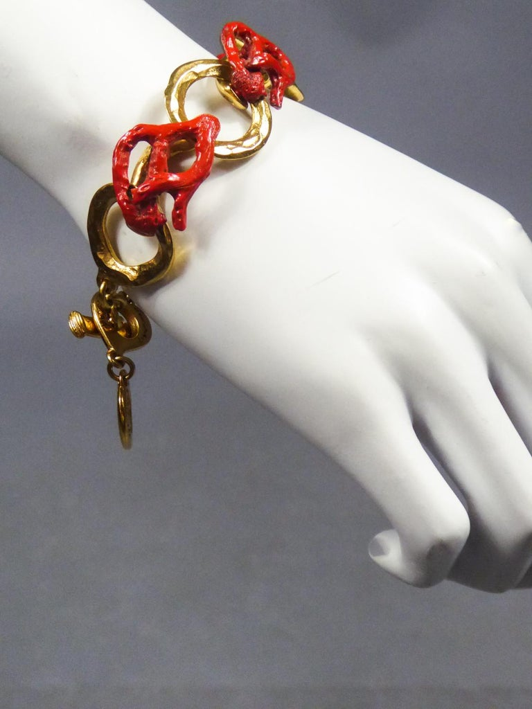 Circa 1980 France Superb bracelet in gilded metal and coral by Robert Goossens for Yves Saint Laurent dating from the 1980s. Bracelet made up of hammered gilded metal rings interspersed with twisted links in coral-style red enameled metal, signed on