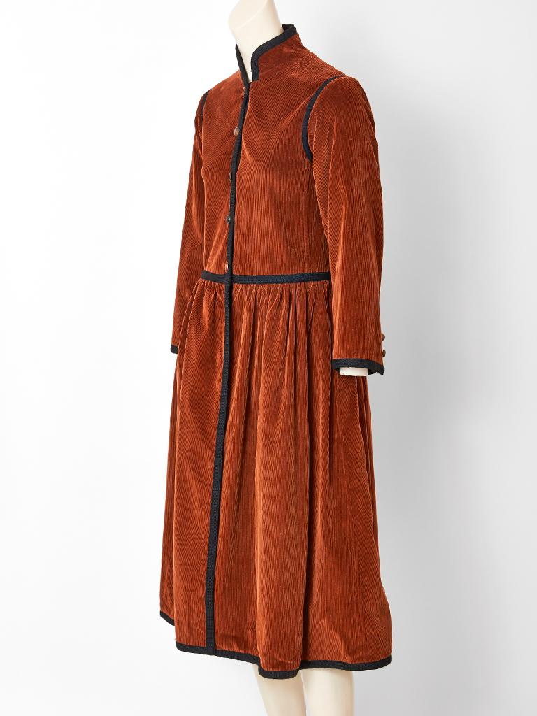 Yves Saint Laurent, Rive Gauche, rust tone, corduroy, Russian Collection, Cossack style coat, having a slightly fitted semi dropped waist bodice, and a gathered skirt. Coat has a Mandarin collar with black braid embellishment, edging the collar,