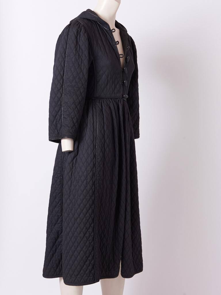 Yves Saint Laurent, Rive Gauche, iconic, Russian collection, black, quilted cotton coat with an attached hood having leather piping detail and black wood toggle button closures. C. 1975-76.