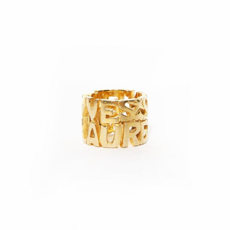Script ring by Yves Saint Laurent  Gold-tone hardware  Cutout logo ring  Heart and star cutout  Condition: Great, some scratching and marks on hardware. (see photos)  Size/Measurements: (approximate)  Size 6.5 6.5cm