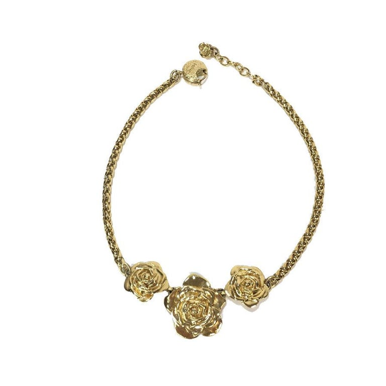 YSL Yves Saint Laurent set: a necklace decorated with 3 roses, a brooch and clip-on earrings, in gilt metal. In good condition, some micro scratches on the whole, slight discoloration on the clips. Made in France, 90's. Dimensions: brooch 2.5 x 2.5