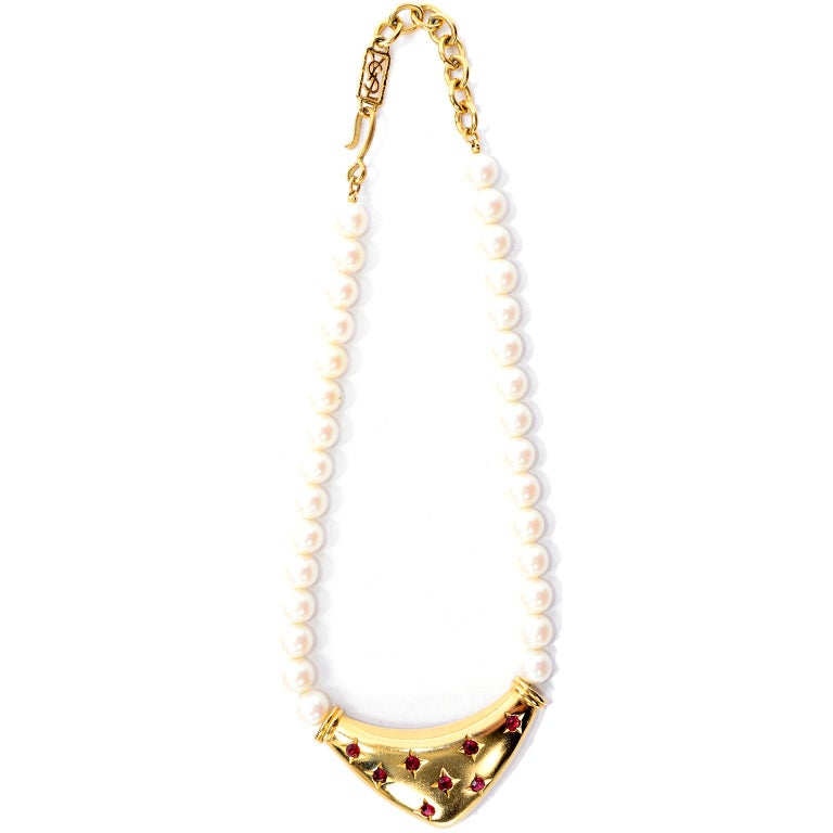 This is a stunning vintage bib necklace from Yves Saint Laurent with a single strand of faux pearls and a gorgeous gold abstract triangle with beautiful red faceted stones that give the appearance of little stars. The necklace has the YSL logo on