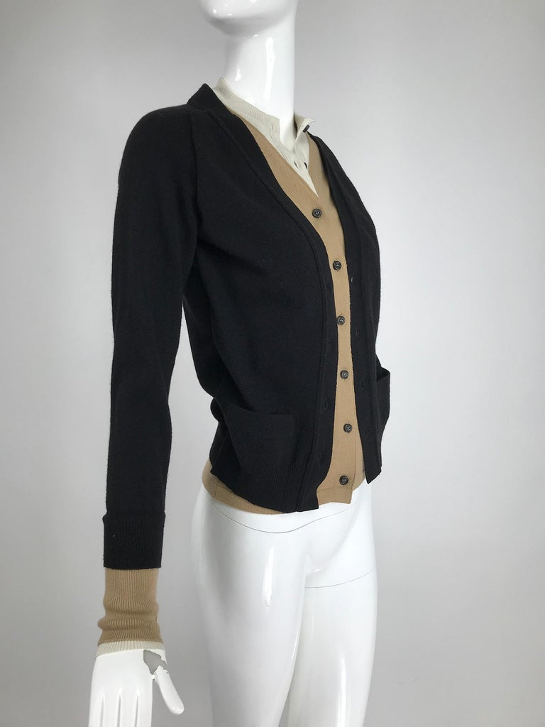 Yves Saint Laurent three in one cropped cardigan sweater. The outer sweater is black, with a v neck front, long sleeves and small front pockets. Ribbed hem and cuffs. The tan layer is only a facing that is stitched to the black sweater, it features