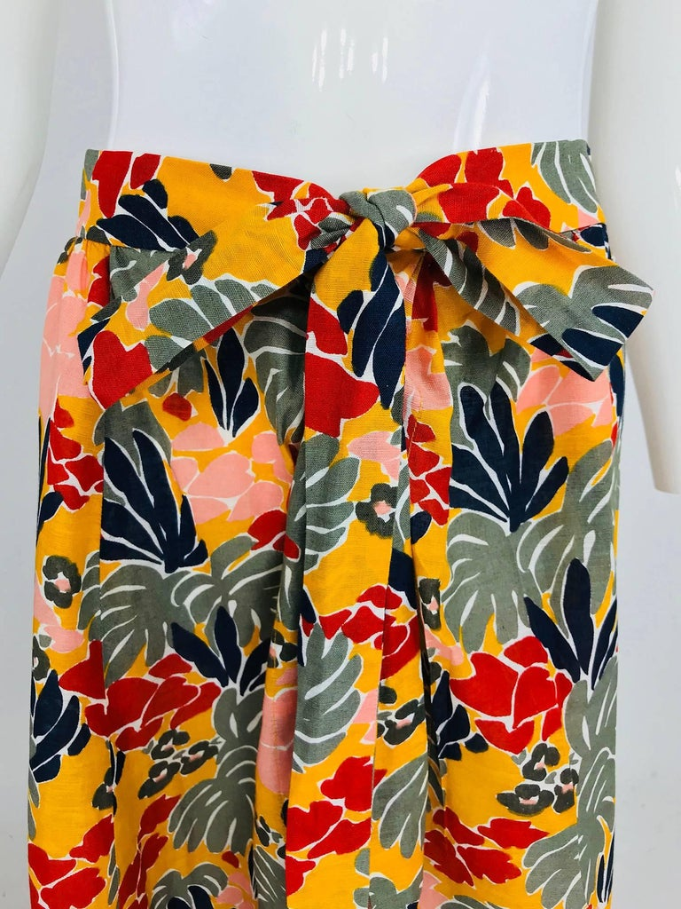 Yves Saint Laurent tropical print cotton maxi skirt 1980s. Lightweight linen skirt is bright tropical print. The skirt has a waist band with attached long ties, gathering at the waist with fullness to the hem. Ties at the waist front and closes with