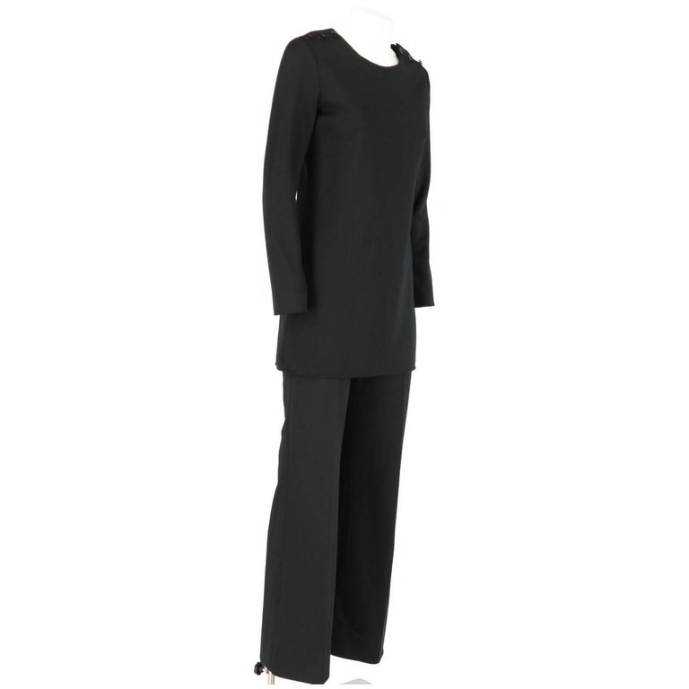 Elegant Yves Saint Laurent black design suit with buttoned blouse and trousers.  Top Height: 76 cm Shoulders: 35 cm Bust: 42 cm Sleeves: 57 cm  Trousers Height: 102 cm Waist: 29 cm